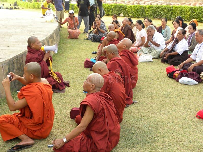 Sarnath, Uttar Pradesh, Índia - 1º de novembro de 2009 monges budistas com as vestes vermelhas e alaranjadas da cor que sentam-se fotografia de stock
