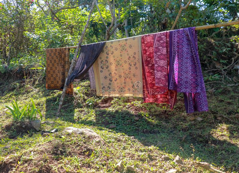 Sarong or Sarung is a traditional outfit worn by Hindus in Bali Island during ceremonies. Colored fabrics draped over the bamboo t royalty free stock image