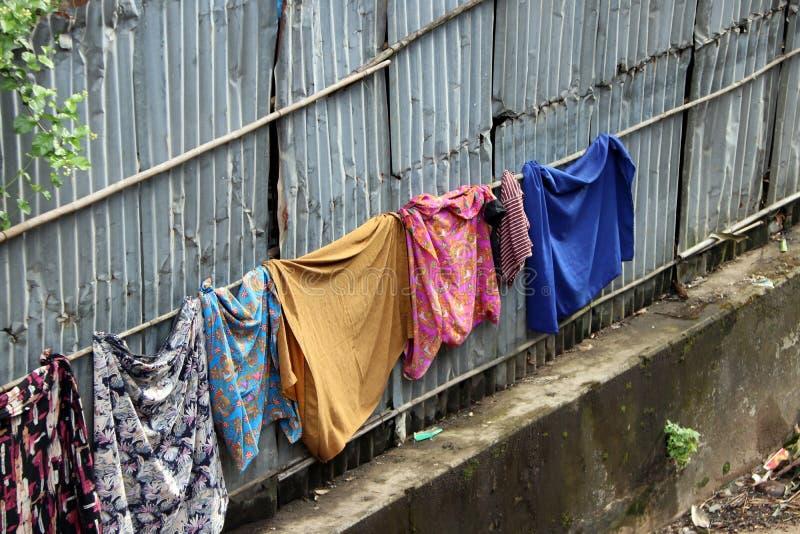 Sarong y lavado y sol de Longeje en la línea de ropa en la pared del cinc foto de archivo