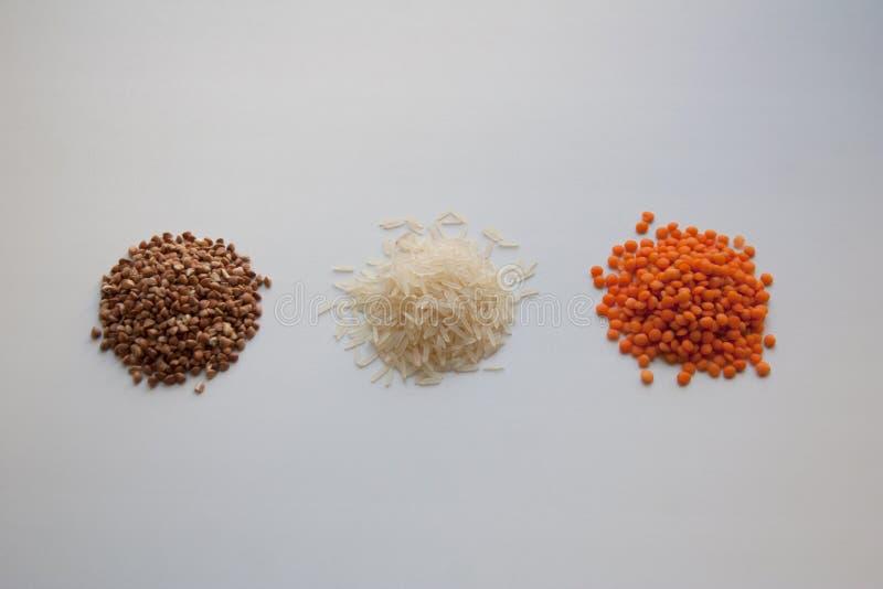 Sarrasin cru, riz basmati et lentilles rouges sur le fond blanc images stock