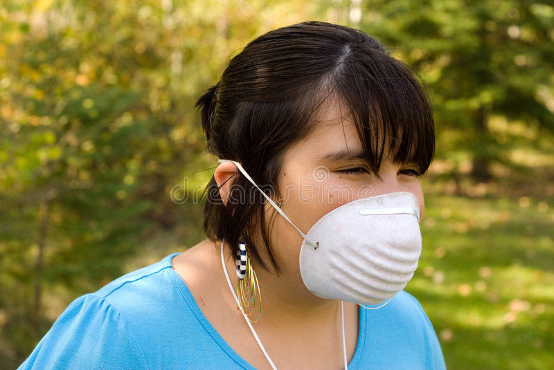 SARS. A young girl wearing a mask to protect herself from SARS stock image