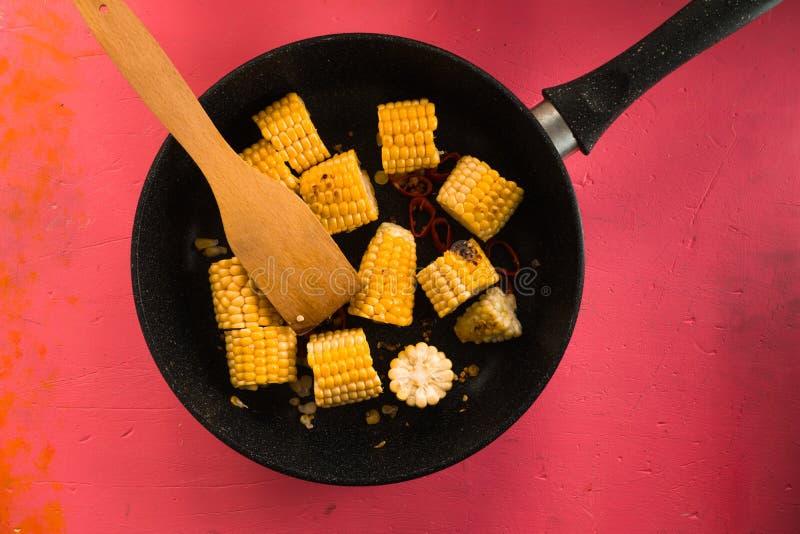 Sartén del arrabio con los pedazos de maíz en una tabla rosada imagen de archivo libre de regalías