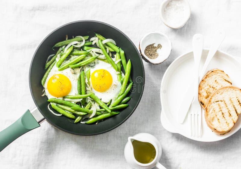 Sartén del desayuno Huevos fritos con las habas verdes Concepto sano de la consumición en el fondo blanco, visión superior foto de archivo libre de regalías