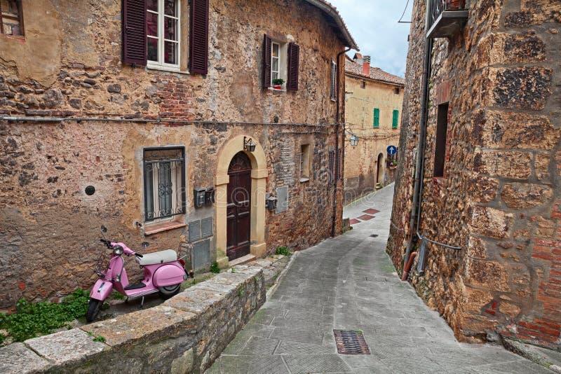 Sarteano, Σιένα, Τοσκάνη, Ιταλία: αρχαία αλέα με ένα ρόδινο μηχανικό δίκυκλο Vespa στοκ εικόνα με δικαίωμα ελεύθερης χρήσης