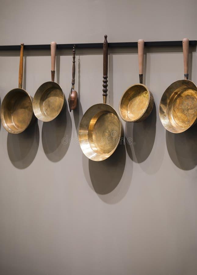 Sartenes viejos decorativos del vintage Colección de sartenes de cobre usados en la pared fotos de archivo