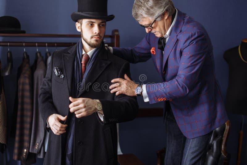 Sarto con il cliente in atelier Vestito su ordine di cucito immagine stock libera da diritti
