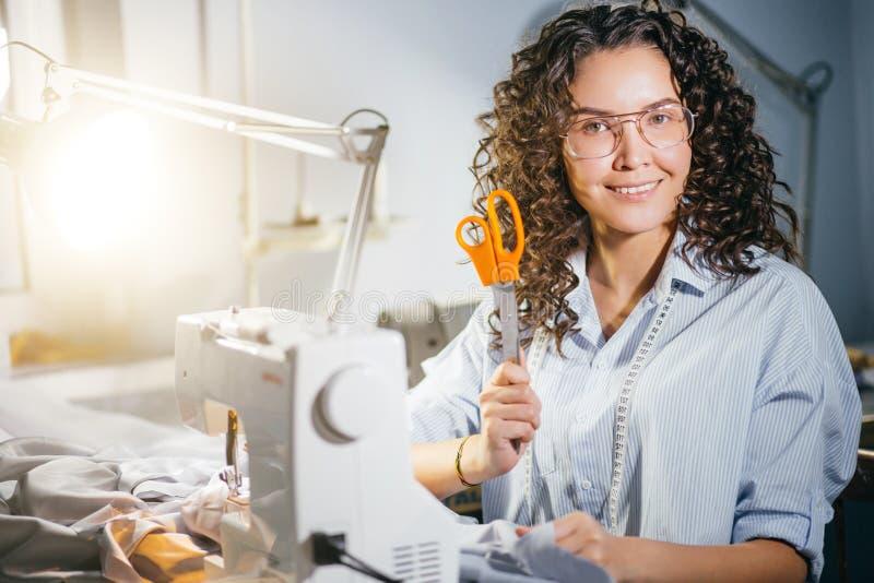 Sarto da donna caucasico che tiene le forbici arancio mentre lavorando allo studio fotografie stock