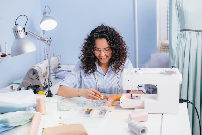 Sarto da donna che si siede sulla sedia e che raccoglie le perle fatto a mano ed artigianato immagini stock libere da diritti
