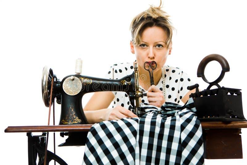 Sarto da donna della donna che pensa e che spiana Facendo uso della macchina manuale di cucito antica immagini stock libere da diritti