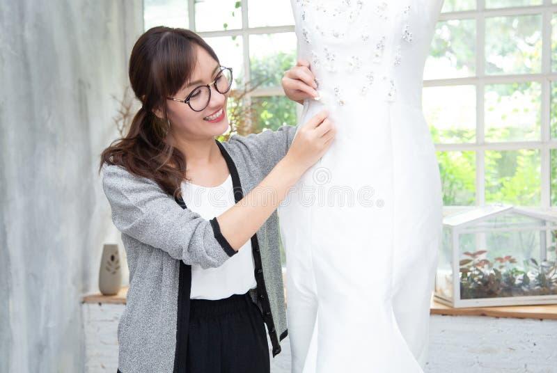 Sarto da donna femminile asiatico attraente sul nuovo modello che adatta vestito sul manichino in studio Misura del manichino di  immagine stock