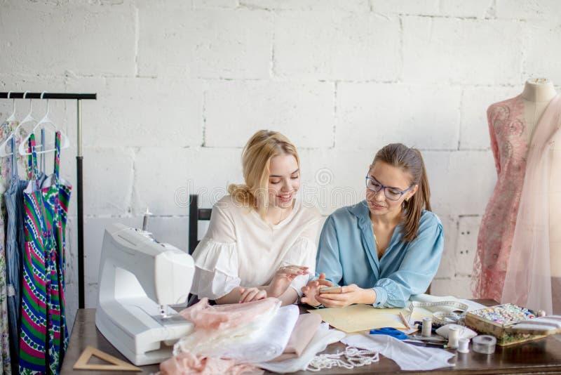 Sarto da donna femminile che mostra progettazione al suo cliente, sedentesi insieme all'officina fotografia stock