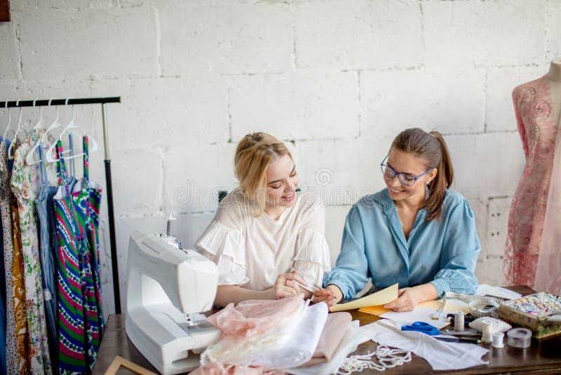 Sarto da donna femminile che mostra progettazione al suo cliente, sedentesi insieme all'officina fotografia stock libera da diritti