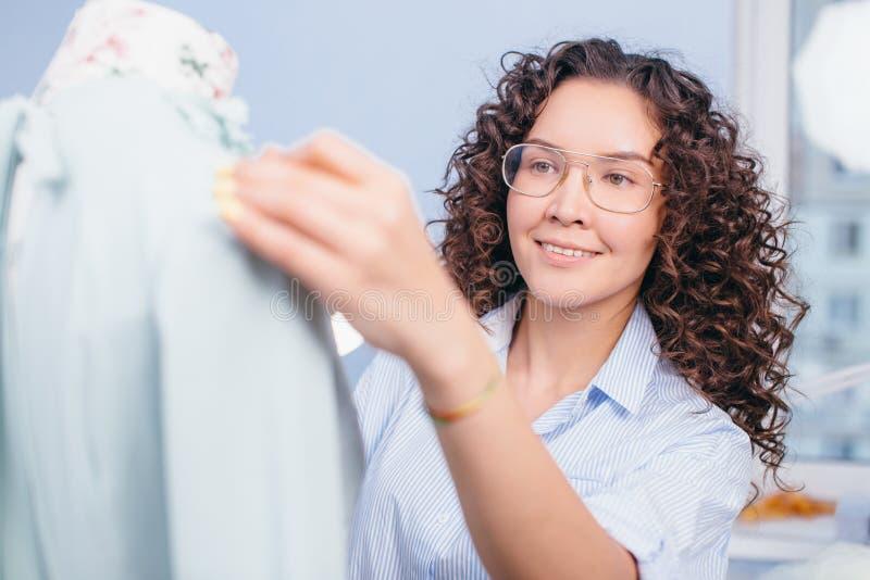 Sarto da donna nel funzionamento di vetro con il manichino imparando come lavorare con il manichino immagini stock