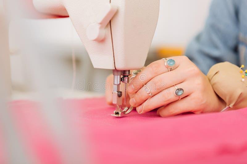 Sarto da donna professionista che infila la macchina per cucire mentre lavorando da solo fotografia stock libera da diritti
