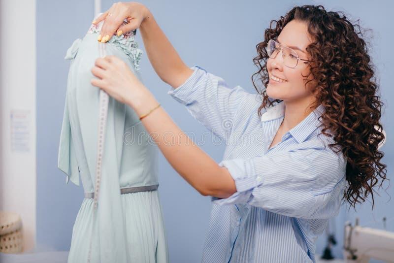 Sarto della donna che lavora con il manichino nella sala spalla di misurazione fotografia stock