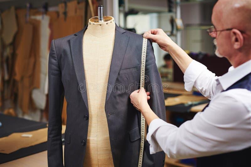 Sarto Measuring Custom Suit in atelier fotografie stock libere da diritti