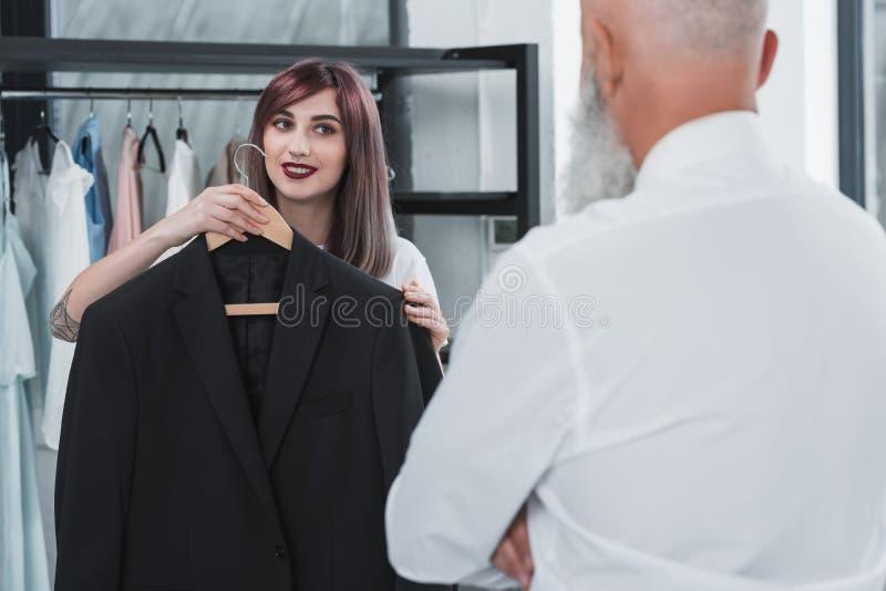 Sarto preoccupantesi che propone uomo anziano per provare sopra il rivestimento del vestito fotografia stock libera da diritti