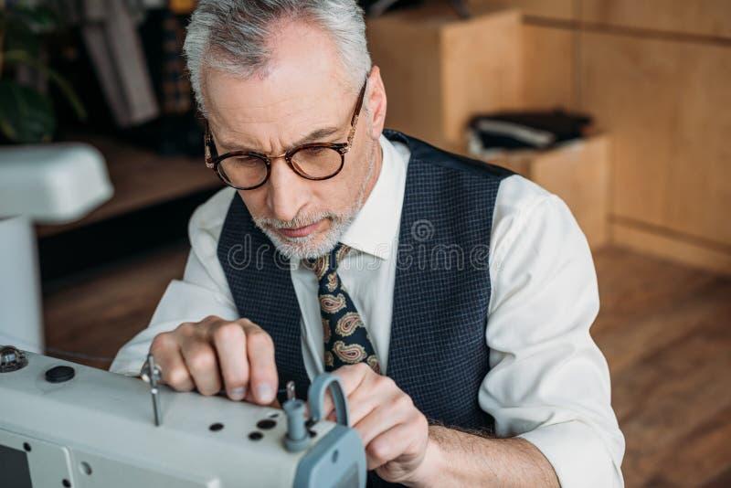 sarto senior che infila ago della macchina per cucire immagine stock libera da diritti