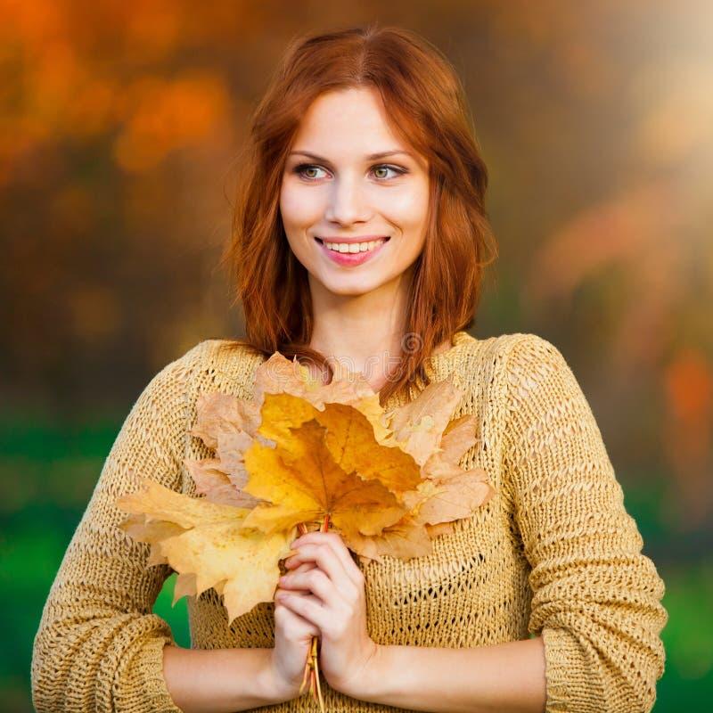 sasha donna dai capelli rossi in maglione beige con le foglie fotografia stock libera da diritti