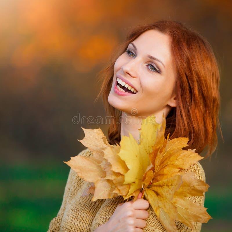 sasha donna dai capelli rossi in maglione beige con le foglie fotografia stock