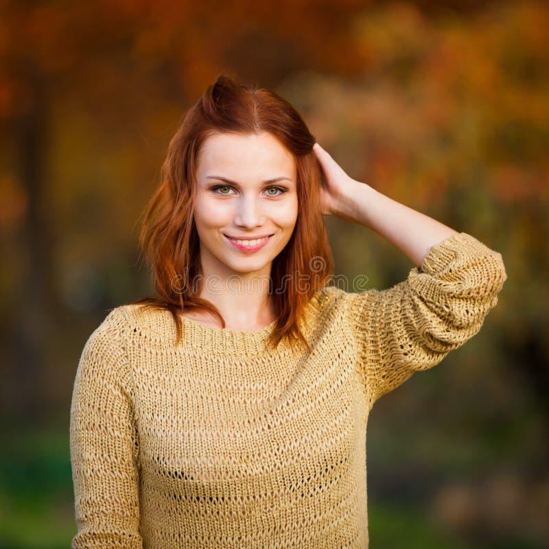 sasha donna dai capelli rossi in maglione beige con le foglie immagine stock