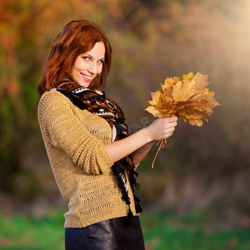 sasha donna dai capelli rossi in maglione beige e sciarpa colorata con fotografia stock