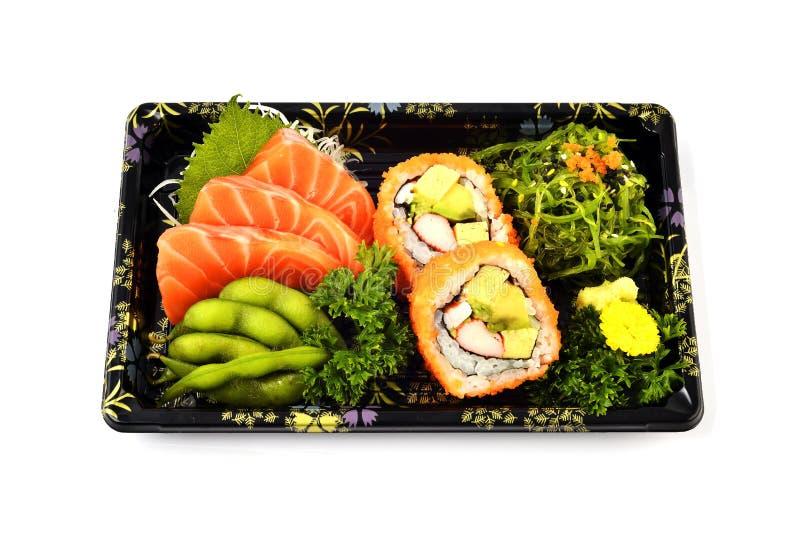 Sashimi και Καλιφόρνια Maki σολομών γεμίζουν με το μπιζέλι περιστεριών και τα πικάντικα τρόφιμα παράδοσης σαλάτας φυκιών ιαπωνικά στοκ εικόνα με δικαίωμα ελεύθερης χρήσης