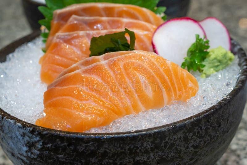 Sashimi σολομών στον πάγο στα μαύρα ιαπωνικά τρόφιμα κύπελλων στοκ φωτογραφία