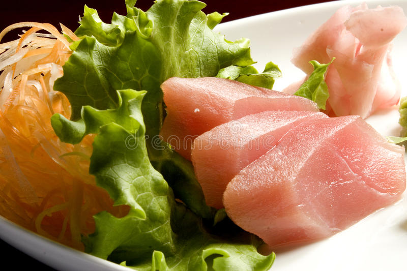 Sashimi. On a platter with carrot and lettuce royalty free stock photography