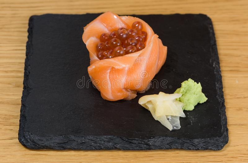 Sashimi composition of fish food, salmon fillets mounted in the shape of a cup, stuffed with caviar, plate served on a slab of. Composition of fish food, salmon stock images