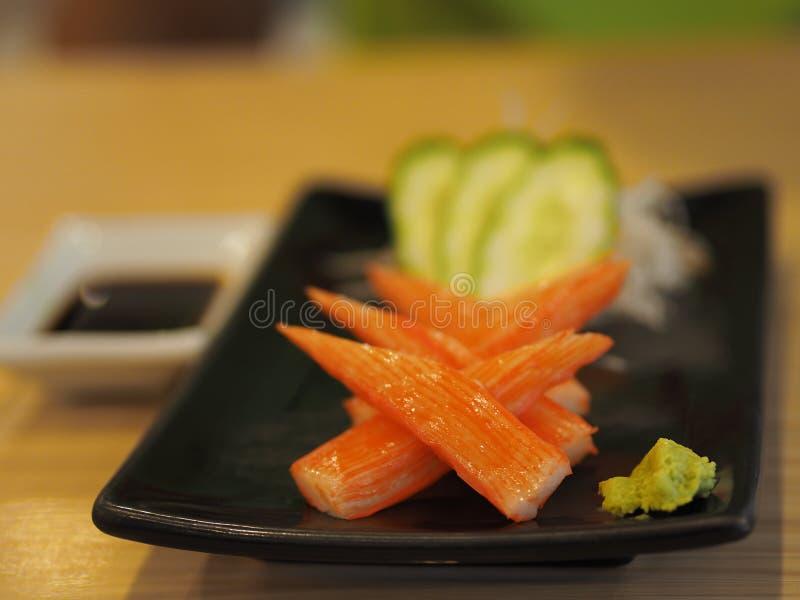 Sashimi cortado da vara do caranguejo de Kani servido com wasabi no prato preto Alimentos japoneses fotos de stock royalty free