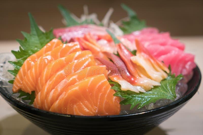 Sashimi cortado mezclado de los pescados en el hielo en cuenco negro Sashimi Salmon Tuna Hamachi Prawn y sistema de la calma de l foto de archivo