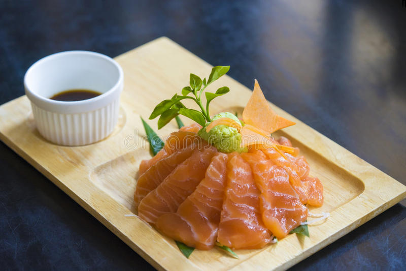 Sashimi crudo di color salmone sul piatto di legno fotografia stock