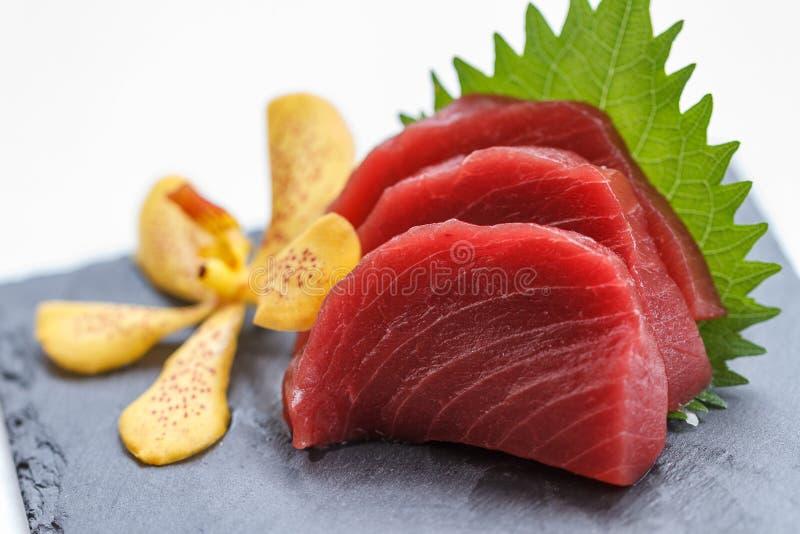Sashimi de Maguro: Maguro crudo cortado Tuna Served con el rábano cortado en la placa de piedra fotos de archivo