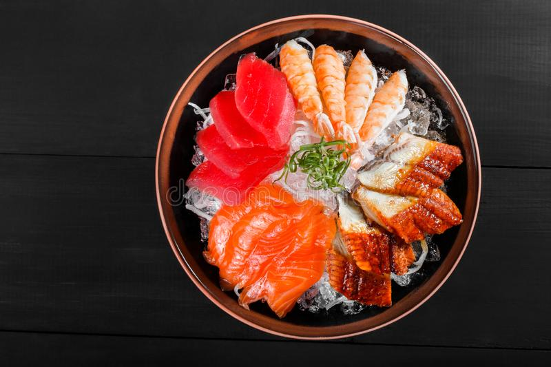 Sashimi japanese food, pieces of tuna, salmon, langoustine, smoked eel with ice in bowl on black wooden background. royalty free stock photography