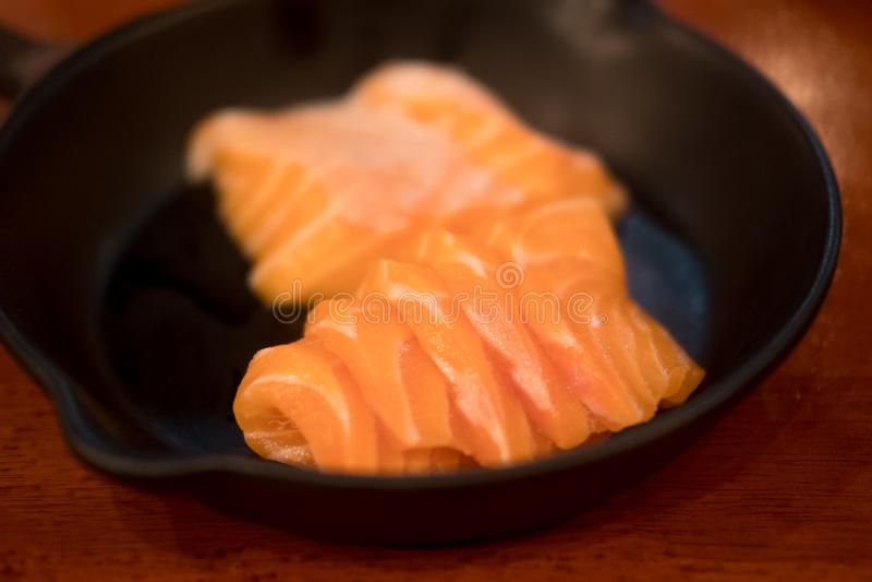 Sashimi japonés de la comida de color salmón en placa negra imagen de archivo