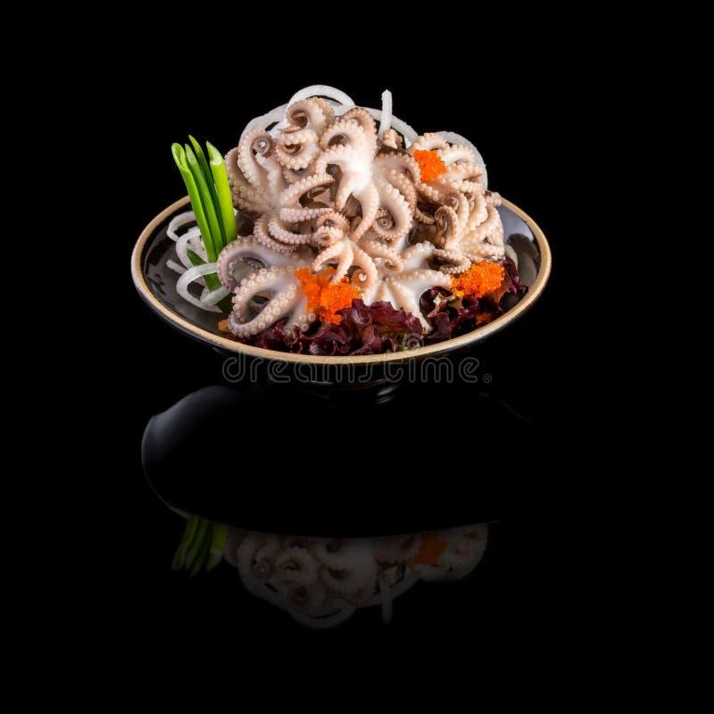 Sashimi mit Krake in einem Schwarzblech Auf einem schwarzen Hintergrundesprit stockfotos