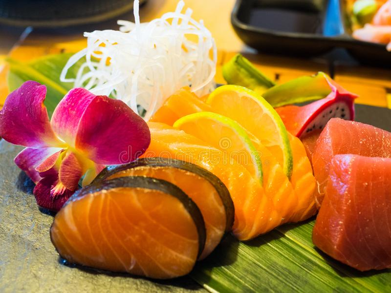 Sashimi mix types of fish on stone plate in Japanese restaurant, fusion and modern Japanese food concept royalty free stock image