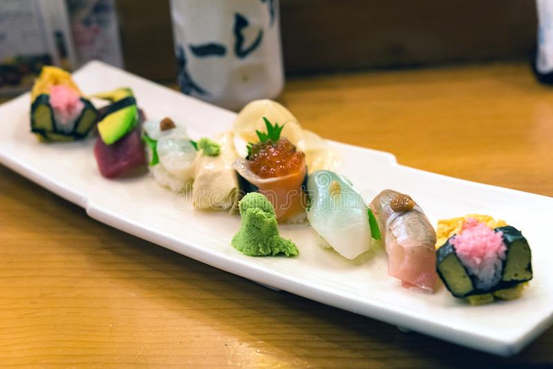 Sashimi sushi set with chopsticks and soy. Close up of sashimi sushi set with chopsticks and soy, Japanese omelette, cucumber and wasabi, Salmon roll , Japanese stock photos