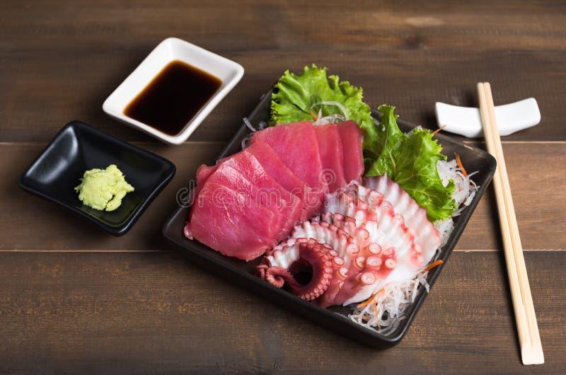 Sashimi tuna and squid with chopsticks on wood background stock photo