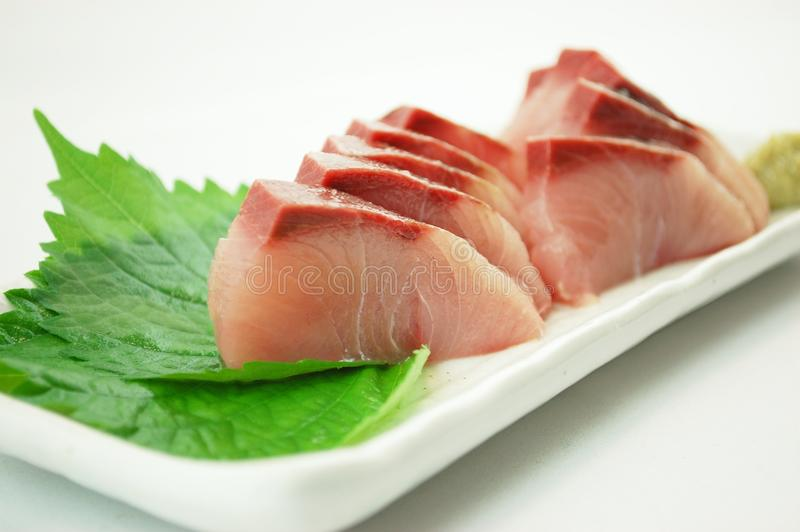Sashimi of Yellowtail. With wasabi sauce and green shiso leaves stock images