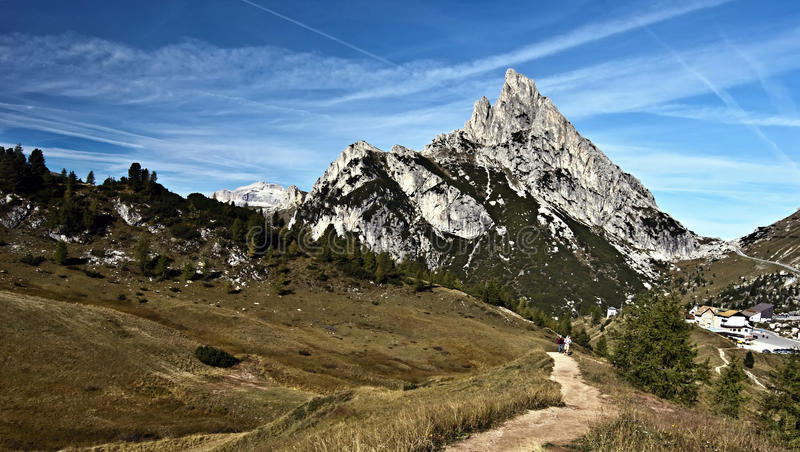 Sass de Stria mountain peak with Passo Falzarego in Dolomites. Sass de Stria mountain peak with Passo Falzarego, hiking trail, meadow and blue sky in autumn stock photography