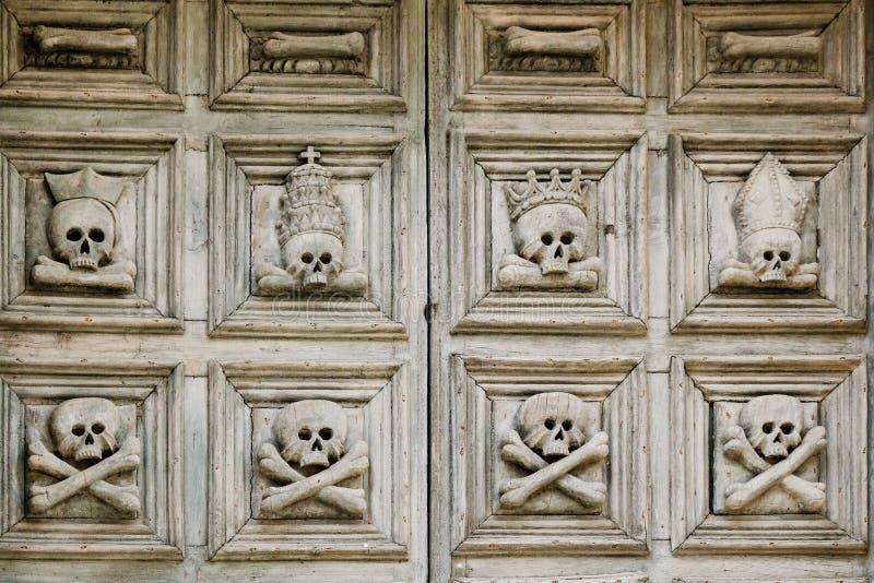 sassi Di $matera Η παλαιά πόρτα στην εκκλησία είναι διακοσμημένη με τα κρανία crossbone στοκ φωτογραφίες με δικαίωμα ελεύθερης χρήσης