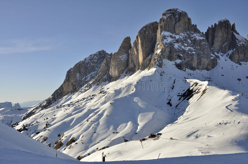Sasso lungo at sunset, dolomites. View of famous mountain in dolomite with steep cliffs and snowy slopes, shot at sunset in bright winter light royalty free stock image