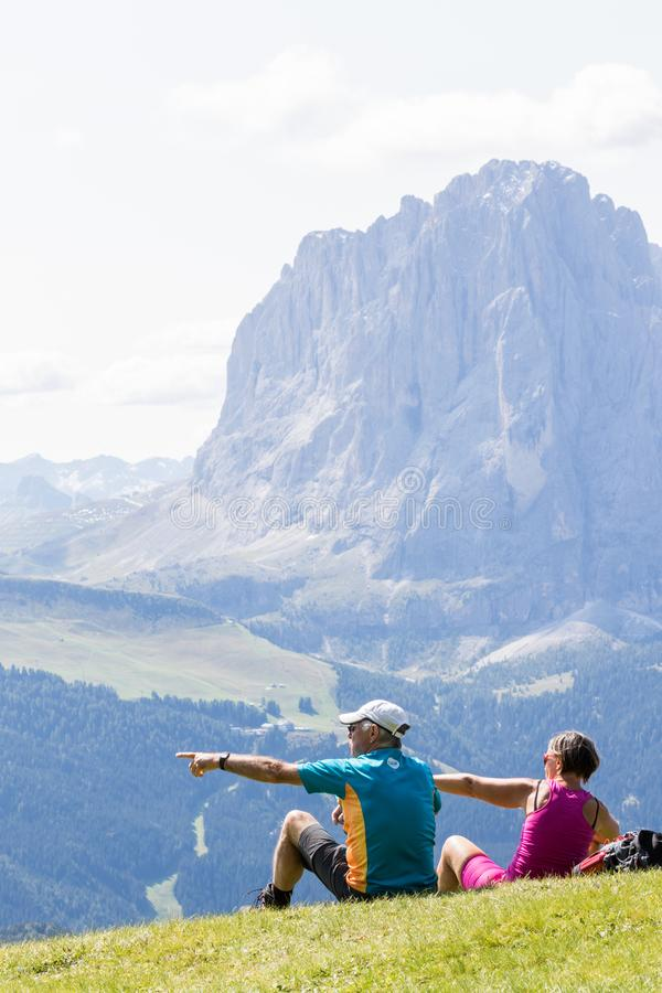 Hikers rest on the lawn admiring the Sassolungo mountain which is part of the Dolomites, Euro stock photo
