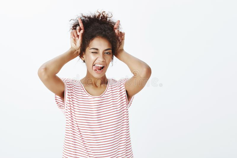 Sassy attractive african woman with afro hairstyle in striped t-shirt, holding index fingers over head mimicking devil stock photos