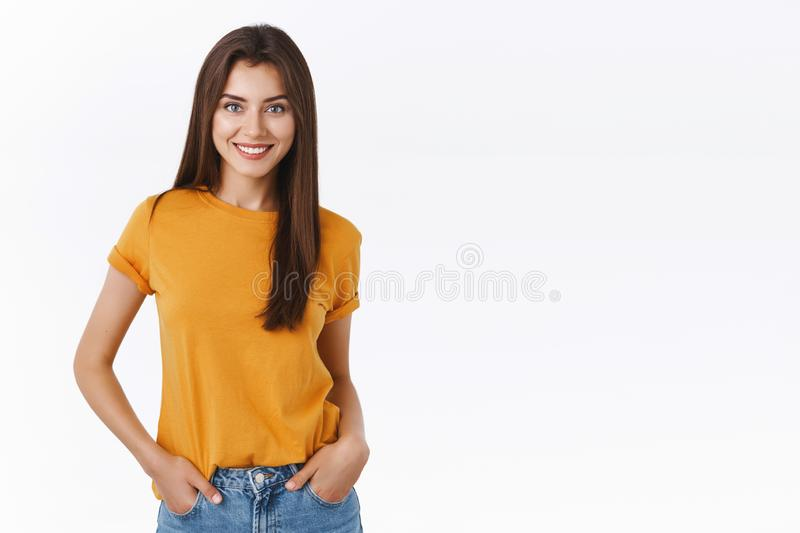 Sassy good-looking feminine brunette woman in yellow t-shirt, hold hands in jeans pockets, smiling self-assured with royalty free stock images