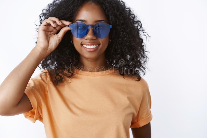 Sassy great-looking african american girl afro hairstyle put on blue cool sunglasses smiling delighted liking new pair. Eyewear enjoying sun walking, partying stock photography