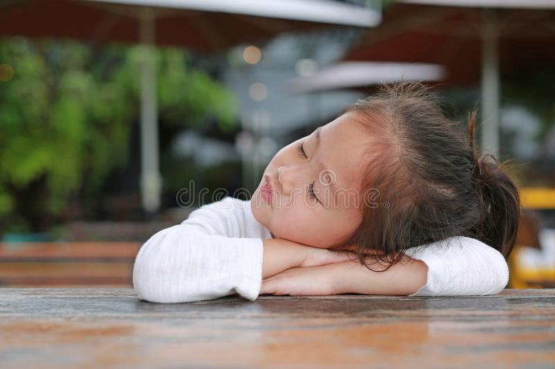 Sassy little Asian child girl with funny face lying on the wooden table stock photos