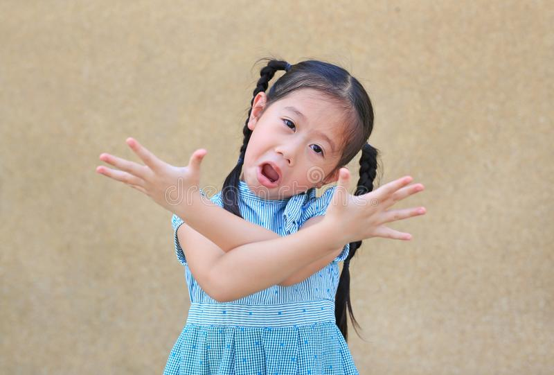 Sassy little Asian kid girl with funny face and expression cross one`s arm royalty free stock images